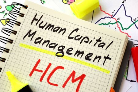 capital: Sign human capital management HCM on a page of notebook.