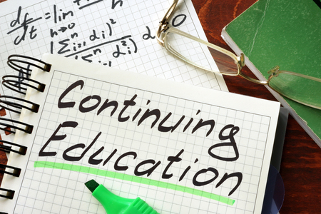 continuing education: Sign continuing education written in a notepad on a table. Stock Photo