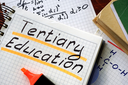 tertiary: Sign tertiary education written in a notepad on a table.