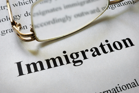 Paper with word immigration and glasses. Law concept.