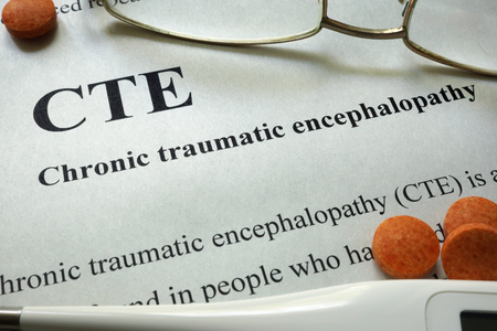 traumatic: Paper with words CTE, Chronic Traumatic Encephalopathy  and glasses. Medical concept. Stock Photo