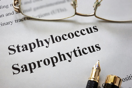 escherichia: Paper with words staphylococcus saprophyticus  and glasses. Medical concept.