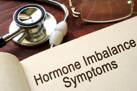 Book with words hormone imbalance symptoms on a table.