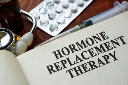 replacement: Book with words hormone replacement therapy on a table.