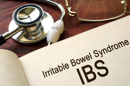Book with words irritable bowel syndrome IBS on a table. Stock Photo