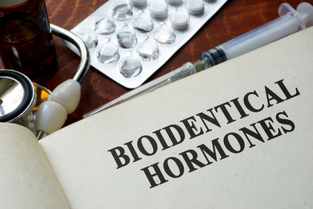 hormone: Book with words bioidentical hormones on a table. Stock Photo