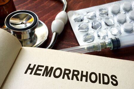hemorrhoid: Book with words hemorrhoids on a table.