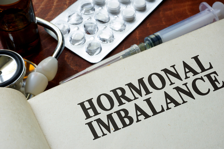 hormonal: Book with words hormonal imbalance on a table. Stock Photo