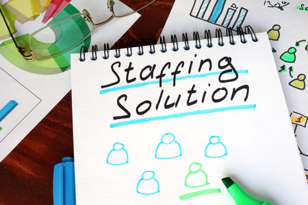 company job: Notepad with staffing solutions on a wooden surface. Stock Photo