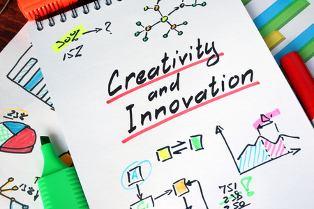 creativity: Notepad with Creativity and Innovation on a wooden surface. Stock Photo