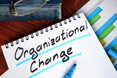 Notepad with Organizational Change on a wooden surface. Standard-Bild