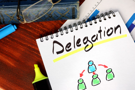delegate: Notepad with Delegation on a wooden surface. Stock Photo