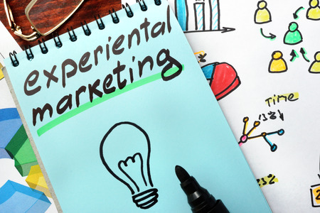 Experiential marketing written in a blue notepad. Stock Photo