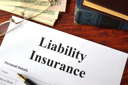 liability insurance: Liability insurance on a wooden table with glasses.