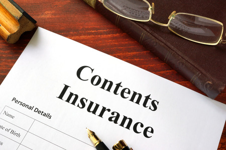 homeowners insurance: Contents insurance policy on a wooden surface with glasses.