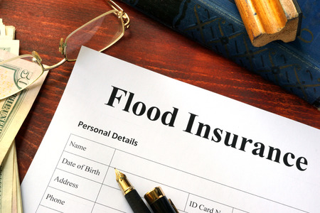 Flood insurance form on a table with a book.
