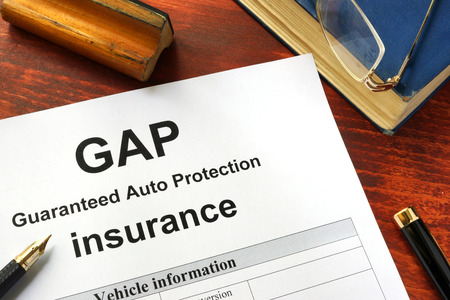 insurer: GAP insurance form on a table with a book.