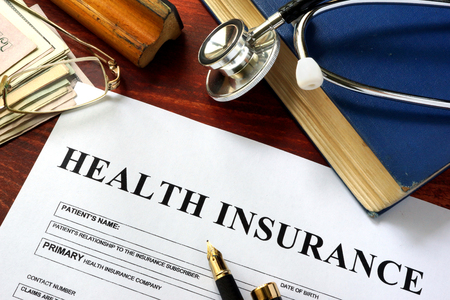 private insurance: Private health insurance on a wooden surface with glasses. Stock Photo