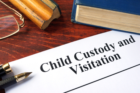 Child Custody and Visitation written on a paper and a book. Imagens