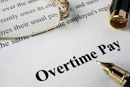 timekeeping: Overtime pay concept written on a paper.