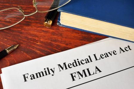 Ley de Licencia Familiar y Médica FMLA y un libro. Foto de archivo