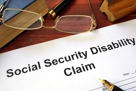 Reclamo por discapacidad de la seguridad social en una mesa de madera. Foto de archivo - 64839240