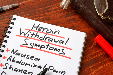 withdrawal: Heroin withdrawal written on a note. Drugs addiction concept.