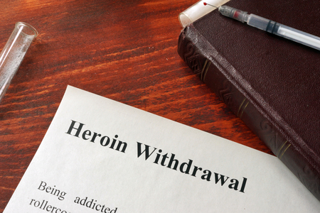 withdrawal: Heroin withdrawal written on a paper. Drug addiction concept.