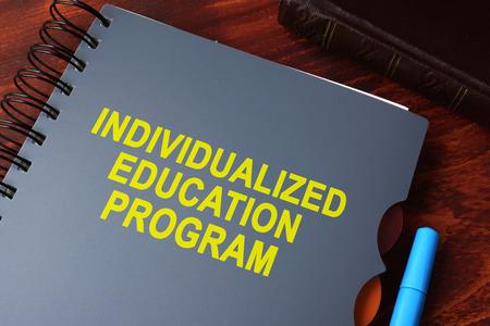 Libro con título programa de educación individualizada (IEP) sobre una mesa. Foto de archivo - 64839223