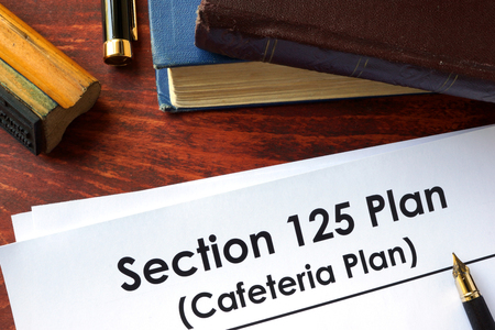 Papers with Section 125 Plan (Cafeteria Plan) on a table.