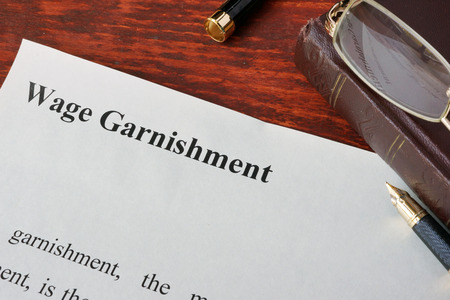 Wage Garnishment definition written on a paper. Banco de Imagens - 66562670