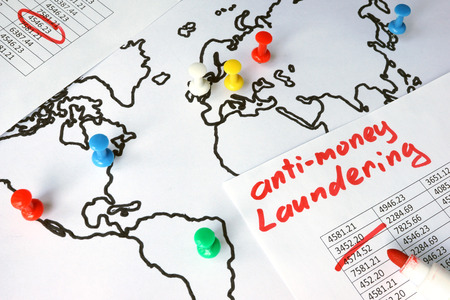 Anti-money laundering (AML) concept. Data and thumb tacks in a map.