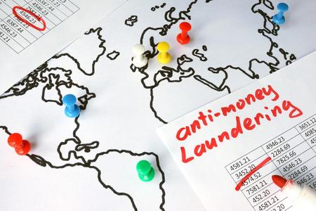 el lavado de dinero (AML) concepto. Datos y el pulgar tachuelas en un mapa.