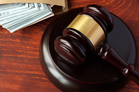 swindle: Corruption in a court concept. A gavel and money on a table.