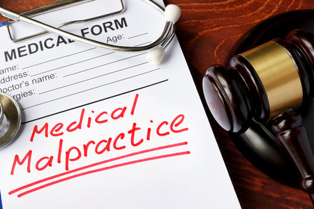 Medical form with words Medical Malpractice and gavel. Stock Photo