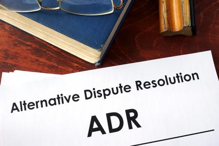 Papiers avec titre Alternative Dispute Resolution (ADR) sur une table.
