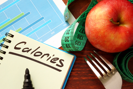 calories: Calories written in a diary. Calorie counting concept.