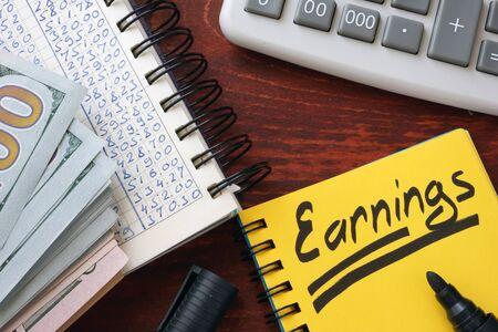 ganancias: Las ganancias escritas en una nota, calculadora y dinero en efectivo.