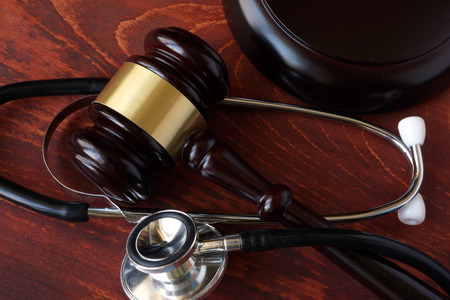 personal injury: Gavel and stethoscope on a wooden surface.