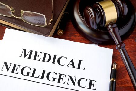 medical occupation: Medical Negligence form, documents and gavel on a table.