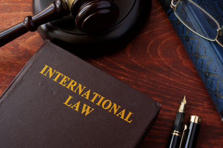 international law: Book with title International law and a gavel. Stock Photo