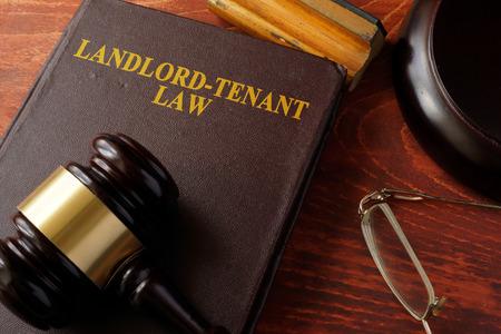 Libro con título Ley de Arrendador-Inquilino y un martillo. Foto de archivo