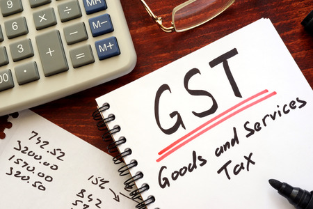 The goods and services tax  (GST) written in a note. Foto de archivo