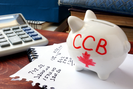 care allowance: Piggy bank with word CCB. Canada child benefit concept.
