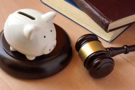 Piggy bank, gavel and books on a table.