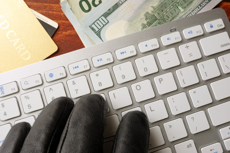 computers online: Hacking concept. Hand in black glove is typing on a keyboard.