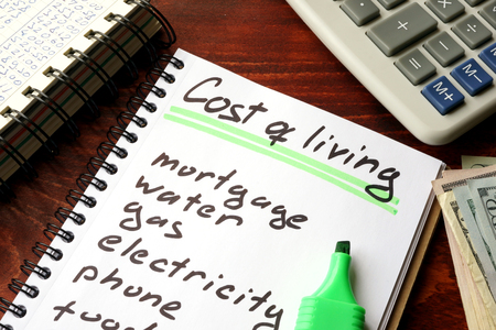 home finances: Cost of living written in a notebook and calculations of home finances. Stock Photo