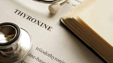 hypothyroidism: Document with title Thyroxine on a table. Stock Photo