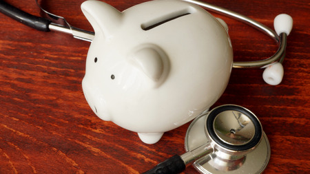 doctor money: Piggy bank and stethoscope. Financial audit concept.
