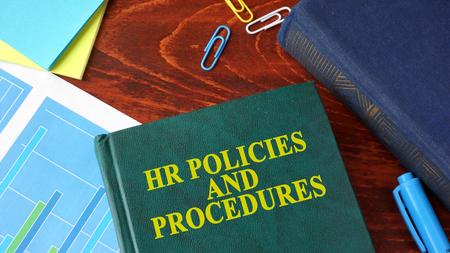 Boek met titel HR-beleid en -procedures op een tafel. Stockfoto